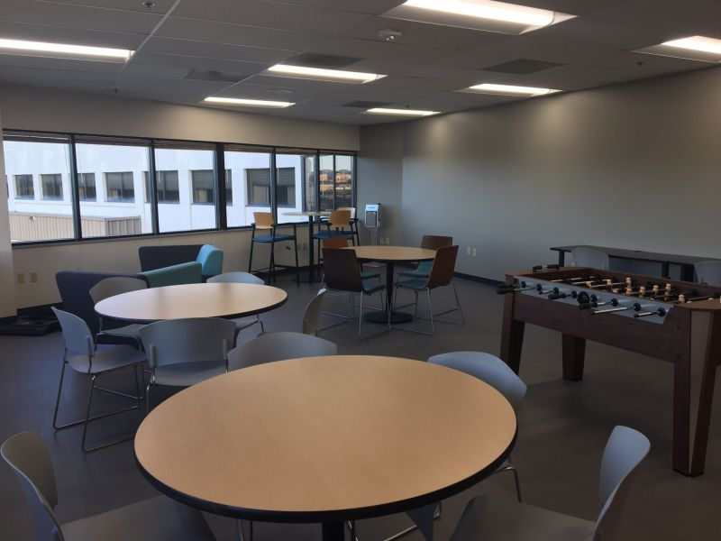 lunch room at American Customer Ccare with lunch tables and chairs and a Foosball table